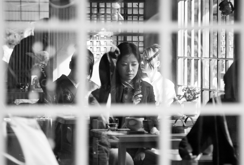 Girl checking her mobile phone as seen through the window of a restaurant in Kyoto